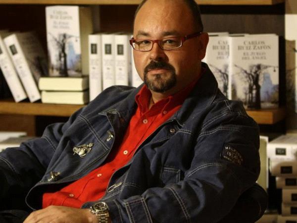 Photographie en portrait de Carlos Ruiz Zafon assis de 3/4