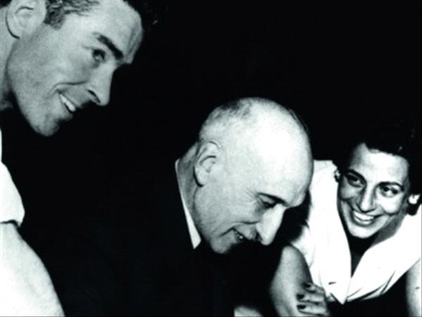Photographie en noir et blanc de François Mauriac en train de signer un livre accompagné de deux autres hommes