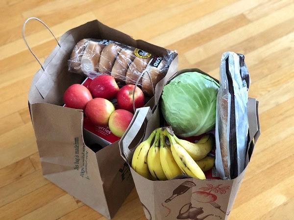 photographie de sac en papier, remplis de nourriture, légumes, fruits et pain