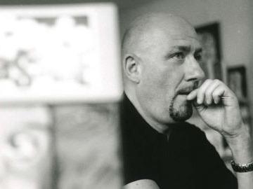 Photographie de Philippe Vandevelde en noir et blanc, assis à un bureau la main près de la bouche
