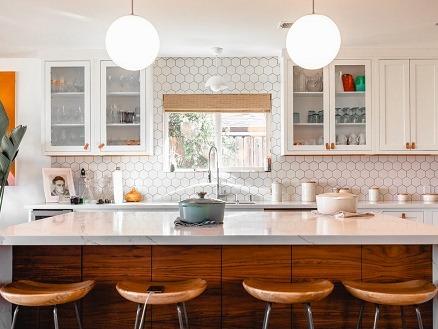 Photographie de face d'une cuisine moderne, avec un ilot central blanc et des chaises de bar en bois