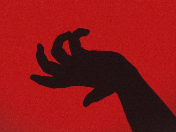 main noire avec doigts crochus sur fond rouge